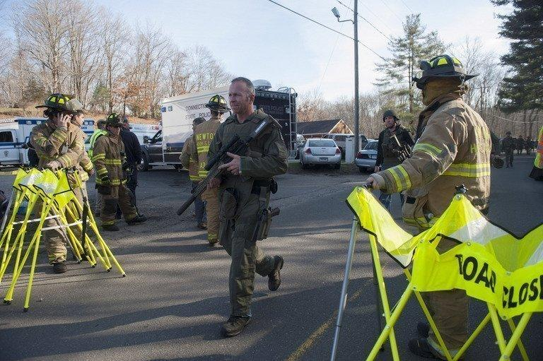 State police walk near the scene of an elementary school shooting in Newtown, Connecticut. At least 26 people, including 20 young children, were killed, and another body was found dead at a second linked crime scene, police said