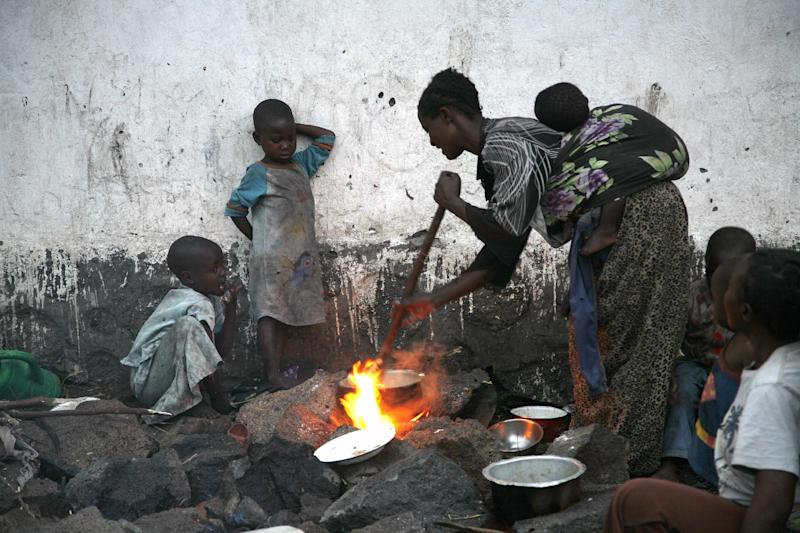 Internally displaced Congolese prepare food at the Mugunga camp outside the eastern Congolese town of Goma, Saturday Nov. 24, 2012. Regional leaders meeting in Uganda on Saturday called for an end to the advance by M23 rebels toward Congo's capital, and also urged the Congolese government to sit down with rebel leaders as residents fled some towns for fear of more fighting between the rebels and army.(AP Photo/Jerome Delay)