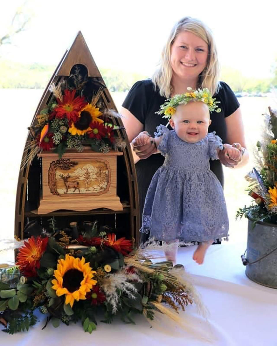 CORRECTS ID TO AUBREA BAKER - In this image provided by courtesy of Janet Baker, Aubrea Baker and her daughter pose for a photo on Sept. 25, 2021, day of funeral for her husband Danny Baker at Tuttle Creek State Park in Manhattan, Kan. The 28-year-old seed hauler from Riley, Kan., contracted COVID-19 over the summer, spent more than a month in the hospital and died Sept. 14. (Courtesy of Janet Baker via AP)
