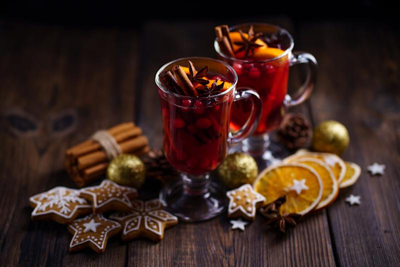 Christmas holidays atmosphere, cold winter day. Warming mood. Mulled wine with cranberry, cinnamon, orange and anise.