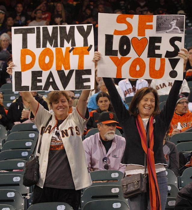 File - In this Sept. 26, 2013 file photo, San Francisco Giants fans hold up signs for Giants' pitcher Tim Lincecum before the start of a baseball game against the Los Angeles Dodgers in San Francisco. Lincecum is staying put with the Giants just as he hoped, reaching agreement Tuesday Oct. 22, 2013, on a $35 million, two-year contract through the 2015 season. The deal is pending a physical, which hadn't been set. (AP Photo/George Nikitin, File)