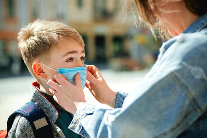 Mother puts a safety mask on her son's face.