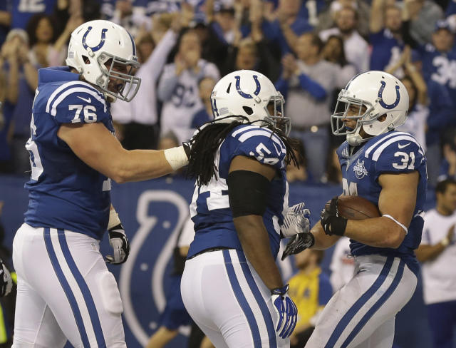 Indianapolis Colts' Donald Brown (31) celebrates with teammates Mario Harvey (54) and Joe Reitz (76) following a 4-yard touchdown run during the second half of an NFL football game against the Tennessee Titans, Sunday, Dec. 1, 2013, in Indianapolis. (AP Photo/Michael Conroy)