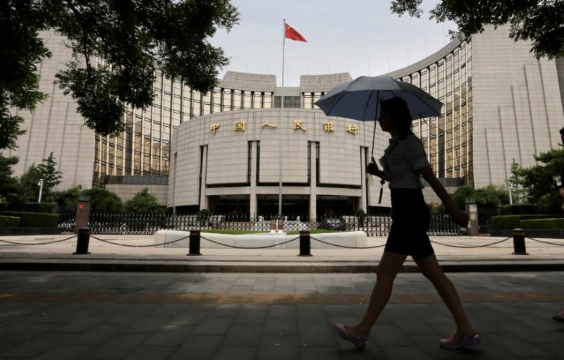 FILE PHOTO: A woman walks past the headquarters of the People's Bank of China (PBOC), the central bank, in Beijing, China
