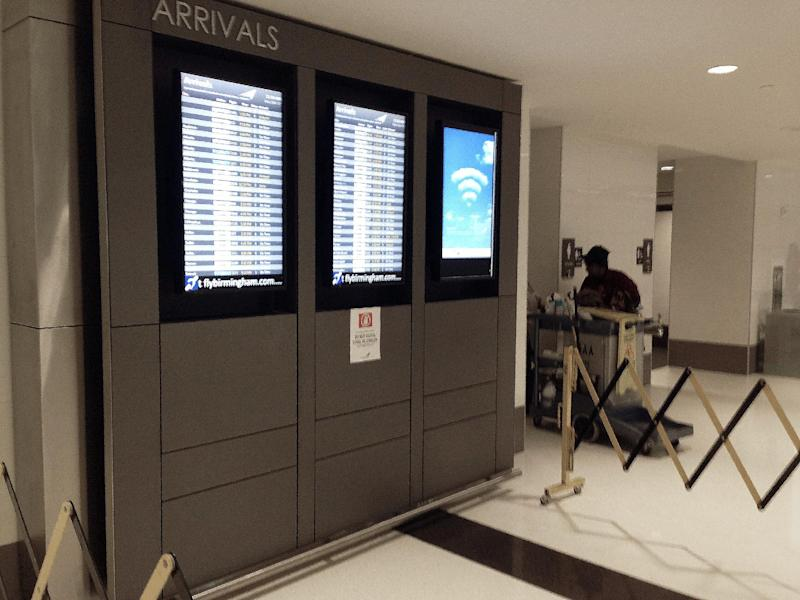 A custodian moves around a large panel video monitor at  Birmingham-Shuttlesworth International Airport, in Birmingham, Ala. on Wednesday, March 27, 2013. Birmingham's airport is still using a the large  300-to 400 -pound panel of video monitors similar to one that tipped over and killed a 10-year-old Kansas boy last week. The approximately 9-foot-tall cabinet was flashing flight information on three screens near baggage claim on Wednesday, five days after a similar display killed Luke Bresette one floor higher in the airport. (AP Photo/Jay Reeves)