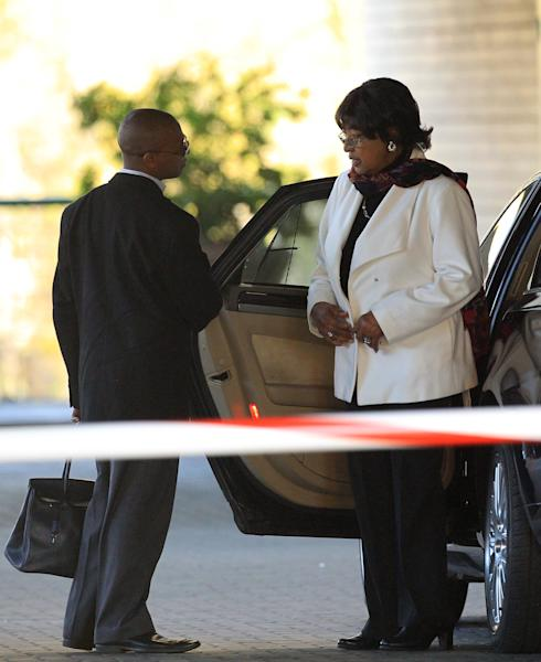 Ex-wife of Nelson Mandela, Winnie Madikizela-Mandela, right, chats with her unidentified driver during her arrival at the Mediclinic Heart Hospital where former South African President Nelson Mandela is being treated in Pretoria, South Africa Wednesday, June 19, 2013. The 94-year-old was hospitalized for a recurring lung infection. (AP Photo/Themba Hadebe)