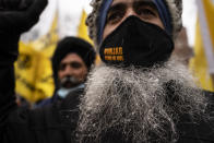 Protesters gather in the snowfall outside the Consulate General of India, Tuesday, Jan. 26, 2021, in the Manhattan borough of New York. Tens of thousands of protesting farmers have marched, rode horses and drove long lines of tractors into India's capital, breaking through police barricades to storm the historic Red Fort. The farmers have been demanding the withdrawal of new laws that they say will favor large corporate farms and devastate the earnings of smaller scale farmers. Republic Day marks the anniversary of the adoption of India's constitution on Jan. 26, 1950. (AP Photo/John Minchillo)