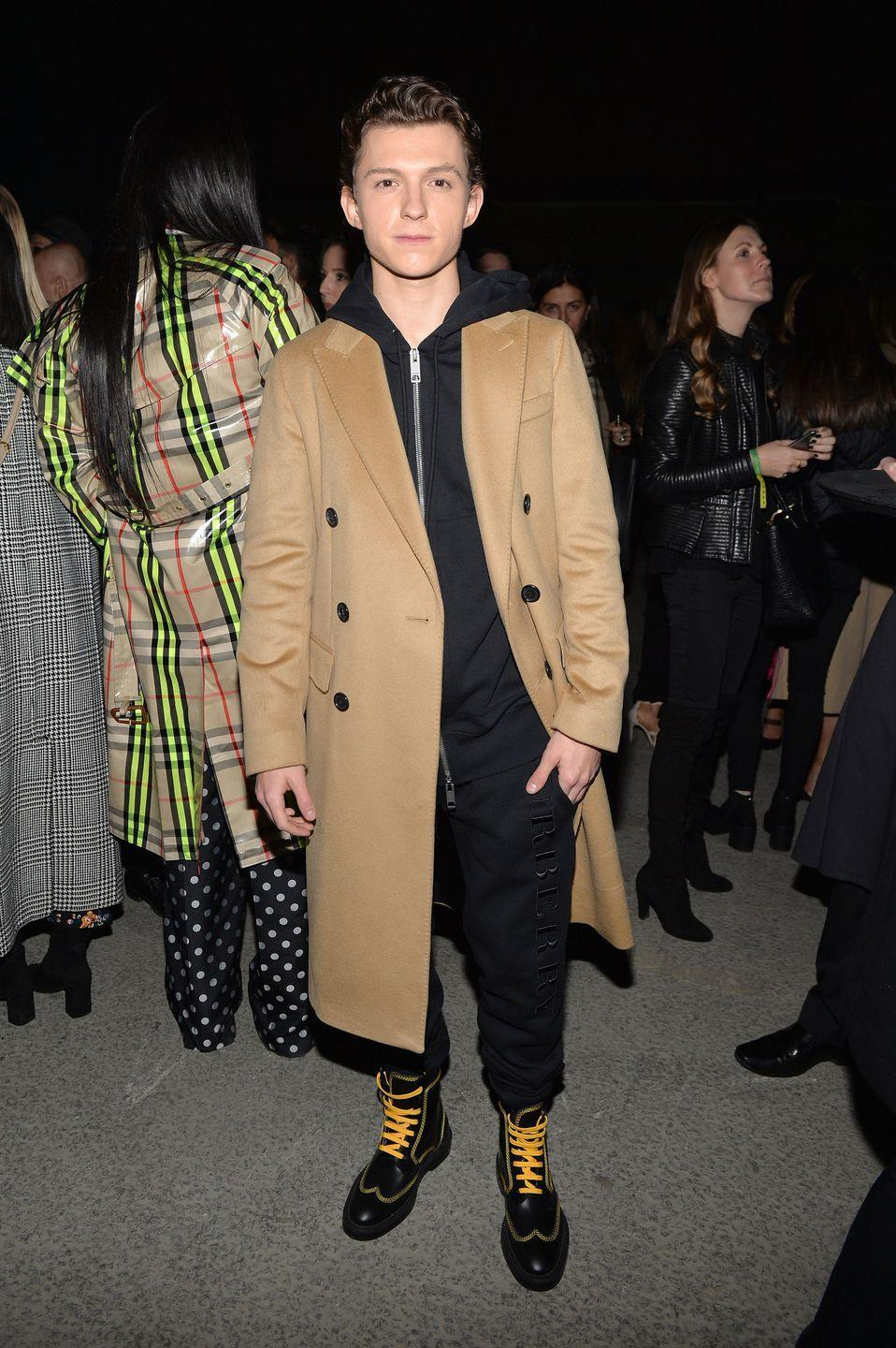 <p>Tom Holland wearing Burberry at the Burberry February 2018 show during London Fashion Week at Dimco Buildings on February 17, 2018 in London, England.</p>