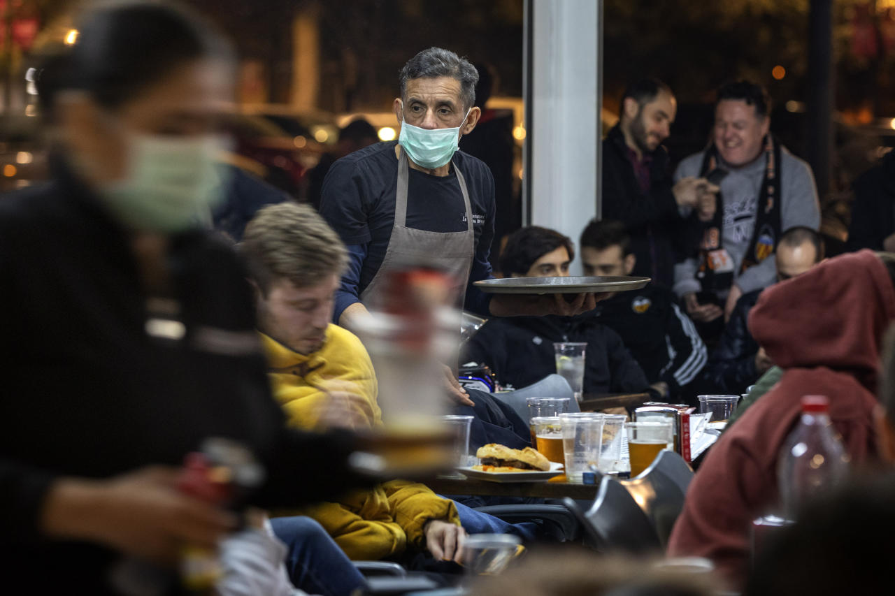 Waiters wearing masks serve food and drink in a terrace outside Mestalla stadium during the Champions League round of 16 second leg soccer match between Valencia and Atalanta in Valencia, Spain, Tuesday March 10, 2020. The match is being in an empty stadium because of the coronavirus outbreak. (AP Photo/Emilio Morenatti)