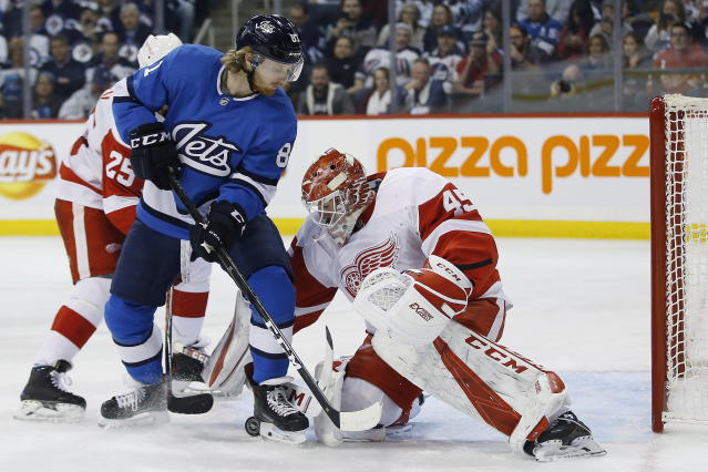 Detroit Red Wings goaltender Jonathan Bernier (45) jumps on a loose puck as Winnipeg Jets' Kyle Connor (81) applies pressure and Wings' Mike Green (25) defends during the second period of an NHL hockey game Friday, Jan. 11, 2019, in Winnipeg, Manitoba. (John Woods/The Canadian Press via AP)