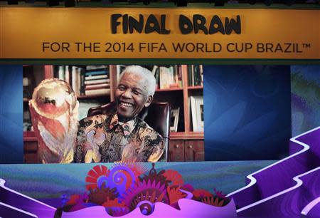 A tribute to former South African President Nelson Mandela is shown on the screen before the draw for the 2014 World Cup at the Costa do Sauipe resort in Sao Joao da Mata