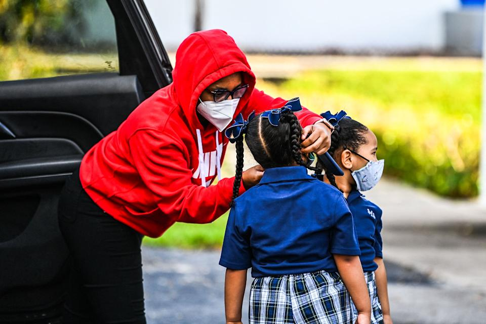 A mother adjusts the facemask of her child as she enters the St. Lawrence Catholic School on the first day of school near Miami, on August 18, 2021. (Photo by CHANDAN KHANNA/AFP)