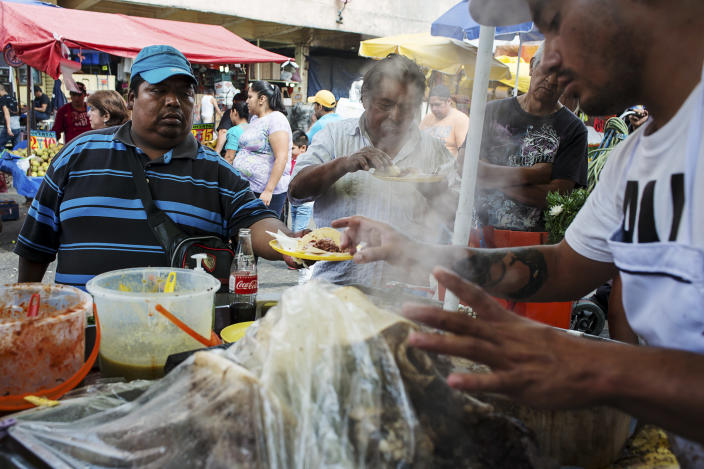 <p>Benito Gutierréz Moreno, 40, gets a snack from a street vendor. He suffers from severe obesity and says he is not aiming to change his diet or lifestyle. (Photograph by Silvia Landi) </p>