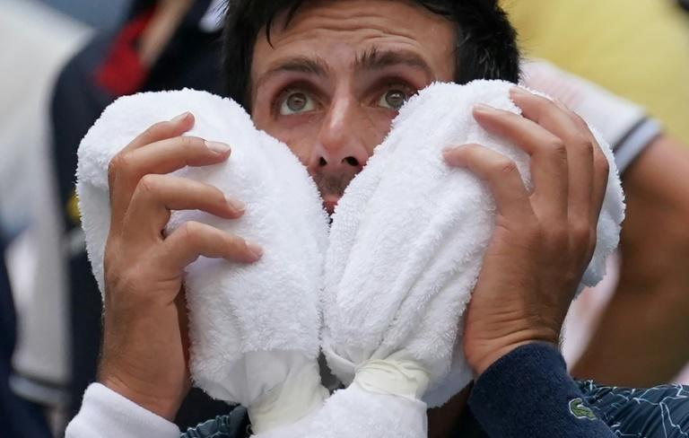 Heat is on: Novak Djokovic takes a break as temperatures hit the 35-degree mark in the first week