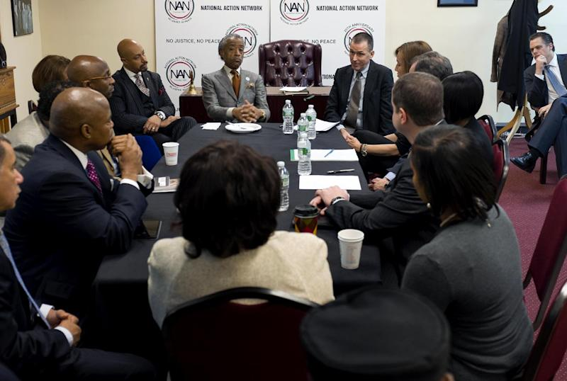 The Rev. Al Sharpton, top center left, listens to Mark Lee, top center right, CEO of Barneys New York, Tuesday, Oct. 29, 2013, at the National Action Headquarters in New York, to discuss allegations of racial profiling after customers who were arrested outside the store after making legal purchases. Two black customers recently claimed they were detained by police on suspicion of credit card fraud after lawfully purchasing expensive items. (AP Photo/Craig Ruttle)