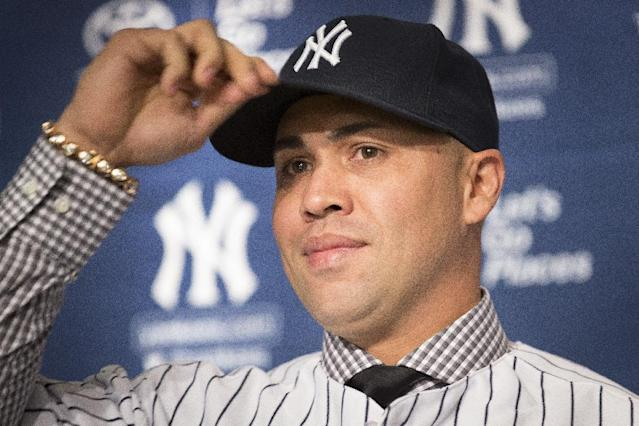 Carlos Beltran tips his hat during a news conference at Yankees Stadium, Friday, Dec. 20, 2013, in New York. The former St. Louis Cardinals outfielder signed with the New York Yankees on a $45 million, three-year contract.(AP Photo/John Minchillo)