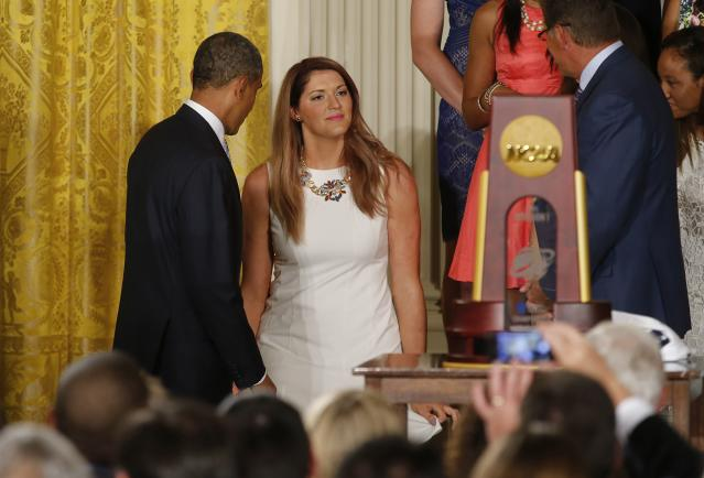 UConn women's basketball star Stefanie Dolson (C) curtsies as she stands between U.S. President Barack Obama (L) and UConn women's head basketball coach Geno Auriemma (R) after Dolson fell off the side of the stage during a ceremony honoring the NCAA basketball champion University of Connecticut Huskies men's and women's basketball teams in the East Room of the White House in Washington, June 9, 2014. Dolson was uninjured in the fall. REUTERS/Jim Bourg (UNITED STATES - Tags: POLITICS SPORT BASKETBALL)