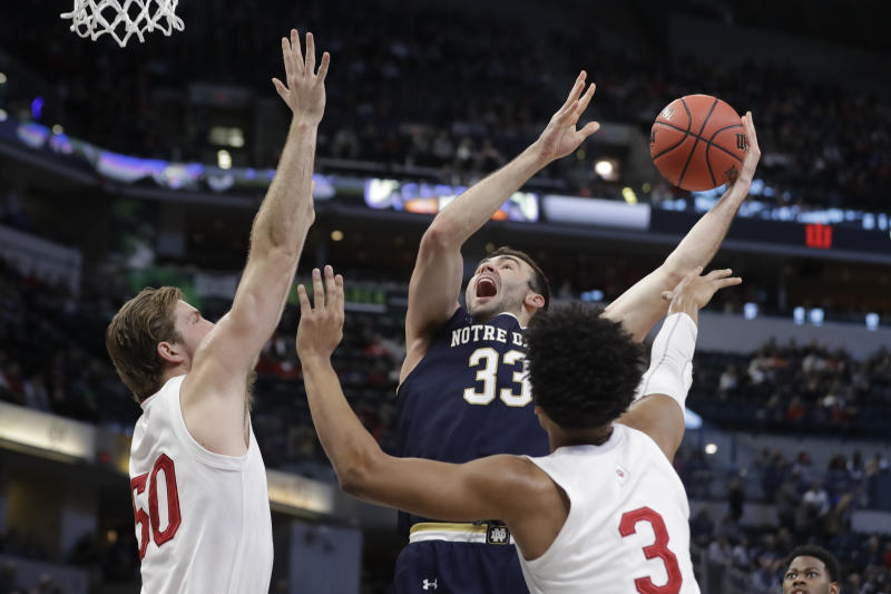 Notre Dame's John Mooney (33) shoots over sIndiana's Joey Brunk (50) and dJustin Smith (3) during the first half of an NCAA college basketball game, Saturday, Dec. 21, 2019. (AP Photo/Darron Cummings)