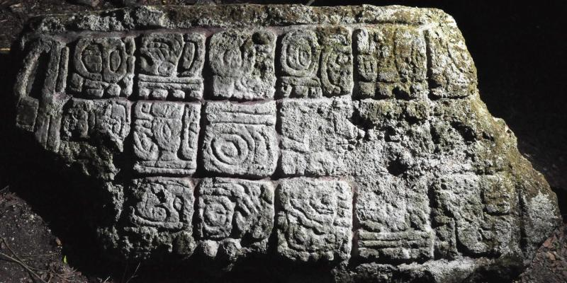 A photograph released to Reuters on August 22, 2014 shows a member of the archaelogical team standing next to a piece of a stela from an ancient Mayan city in Lagunita
