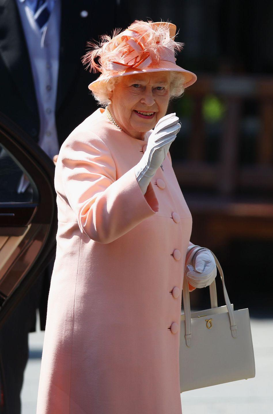 <p>The Queen loves a bright look. Here she is in a peachy-pink coat and hat outfit for her granddaughter's big day.</p>