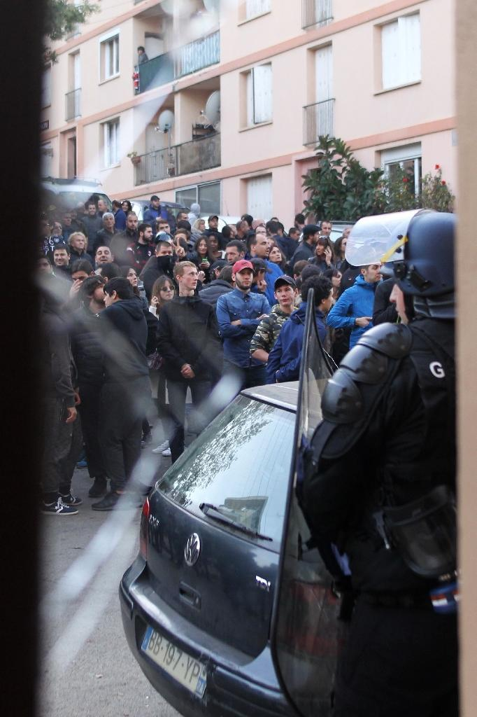 Police officers stand guard as demonstrators protest at the Jardins de l'Empereur housing estate in Ajaccio on December 26, 2015 (AFP Photo/Yannick Graziani)