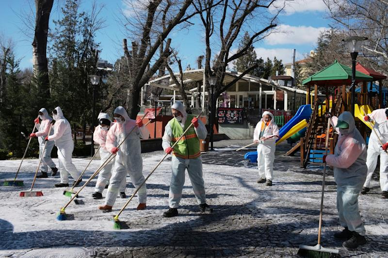 Municipality workers wearing face masks and protective suits disinfect Kugulu public garden amid the coronavirus outbreak, in Ankara, Turkey, on March 17.