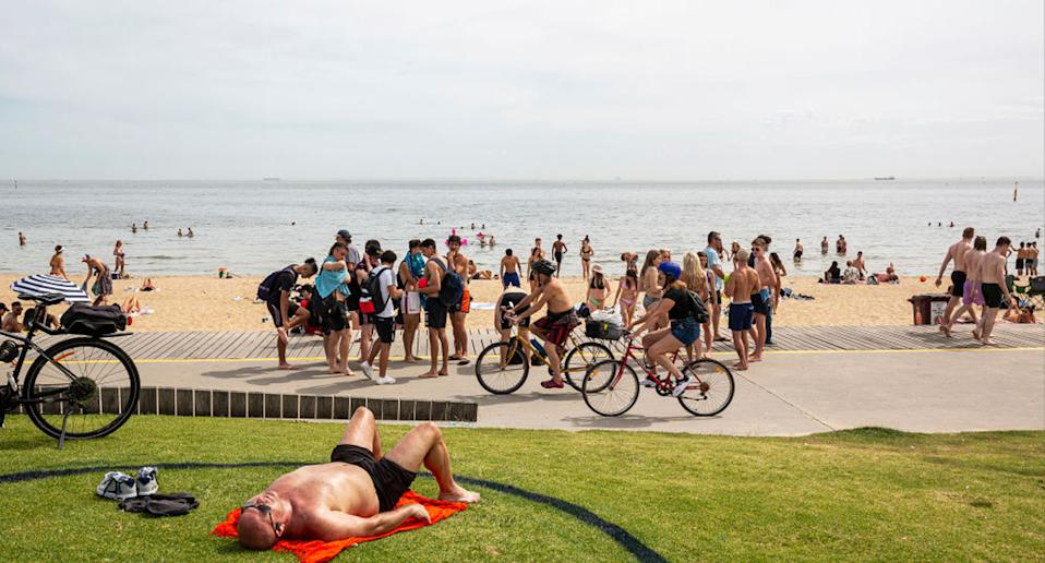 People enjoy the weather at St Kilda beach in Melbourne — that's the caption