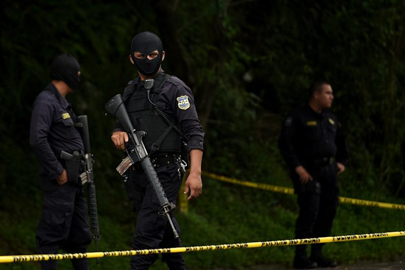 Members of the National Civil Police stand guard next to a crime scene in Cojutepeque, 30 km east of San Salvador on October 21, 2015