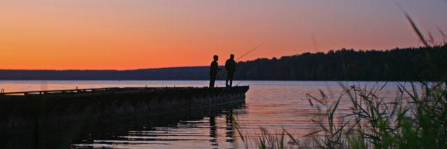 Father and son fishing from a wooden pier.