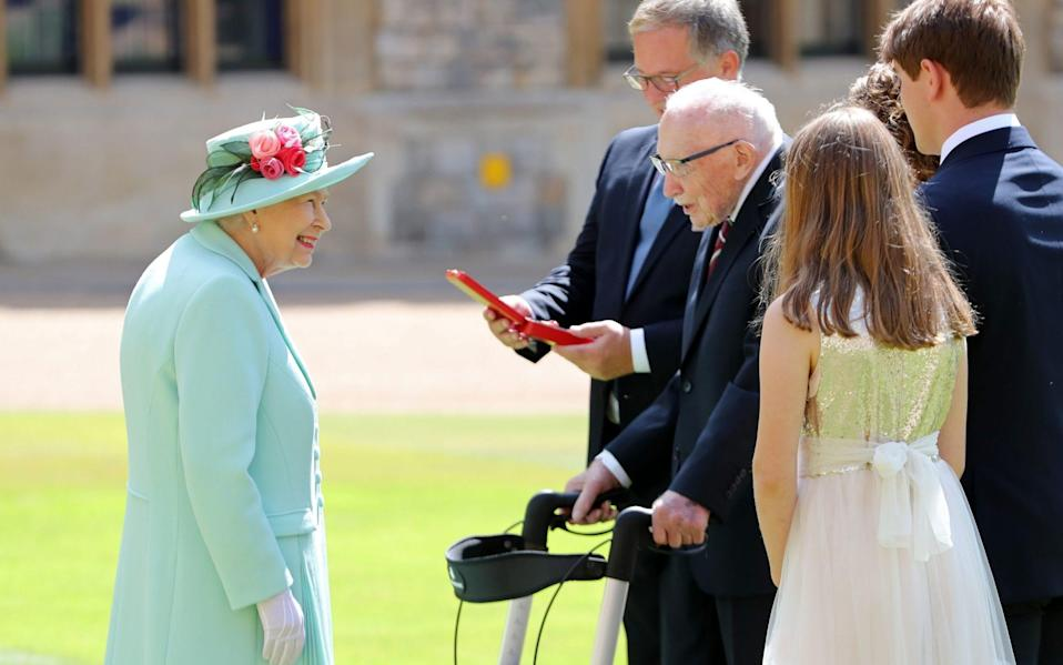 Queen Elizabeth II talking Captain Sir Thomas Moore and his family after awarding his knighthood during a ceremony at Windsor Castle. -  Chris Jackson/PA Wire