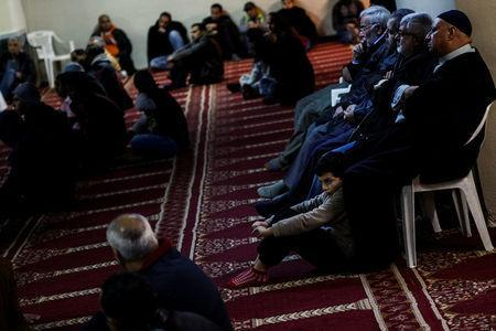 A boy sits next to his father as muslims living in Greece attend Friday prayers at the Masjid Al-Salam makeshift mosque in Athens, Greece, February 3, 2017. REUTERS/Alkis Konstantinidis