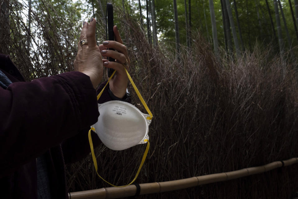 A tourist holds a mask while taking pictures of the Arashiyama Bamboo Forest in Kyoto, Japan, March 18, 2020. (AP Photo/Jae C. Hong)
