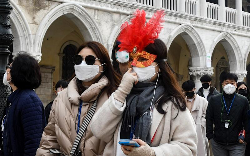 Tourists in Venice sport the city's traditional masks – as well as more modern face coverings - Getty