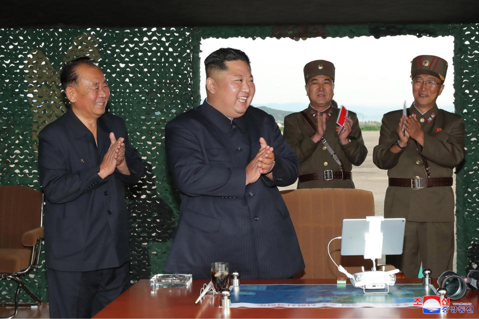 """This Saturday, Aug. 24, 2019, photo provided Sunday, Aug. 25, by the North Korean government, shows North Korean leader Kim Jong Un, center, claps hands as Kim watches the test firing of an unspecified missile at an undisclosed location in North Korea. North Korea fired two suspected short-range ballistic missiles off its east coast on Saturday in the seventh weapons launch in a month, South Korea's military said, a day after it vowed to remain America's biggest threat in protest of U.S.-led sanctions on the country. The content of this image is as provided and cannot be independently verified. Korean language watermark on image as provided by source reads: """"KCNA"""" which is the abbreviation for Korean Central News Agency. (Korean Central News Agency/Korea News Service via AP)"""