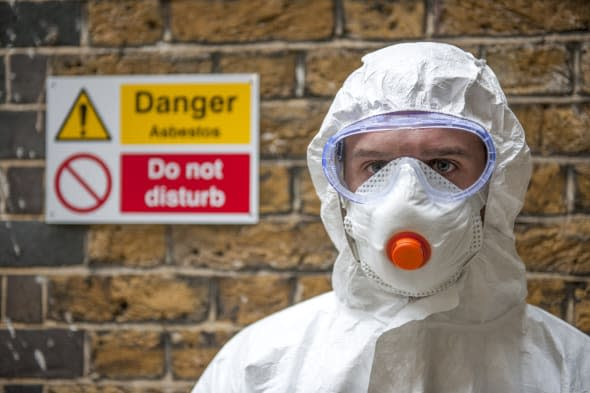 Asbestos protection. Worker wearing protective clothing, a face mask and safety goggles.