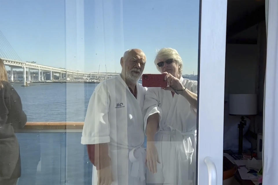 In this image from a video taken on Feb. 9, 2020, Cheryl Molesky and Paul Molesky film selfie video on balcony of the Diamond Princess, anchored at a port in Yokohama, near Tokyo. Even during the quarantine, it can seem like the couple are still on vacation. (Cheryl and Paul Molesky via AP)