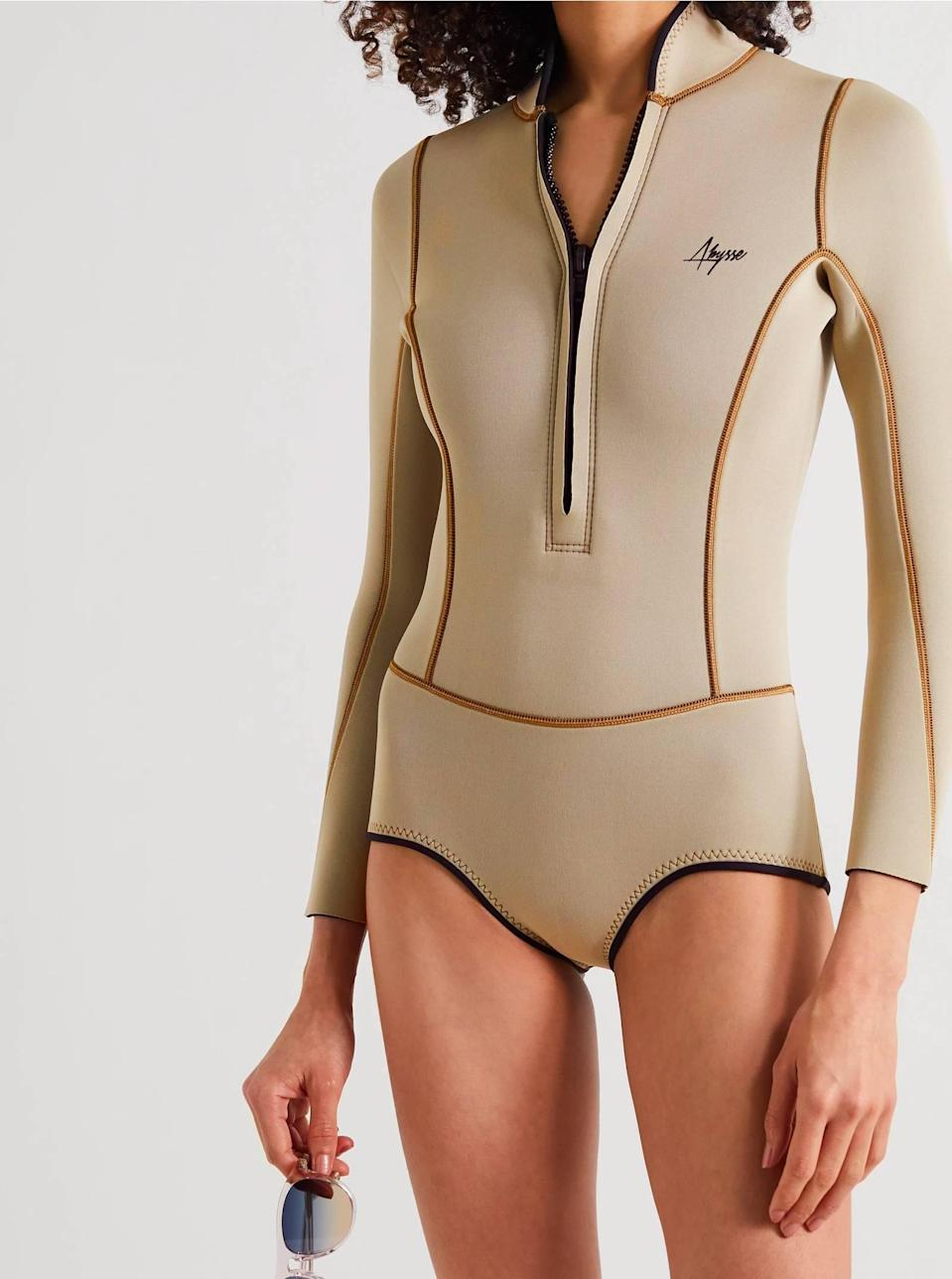"""The taupe color, the brief bottoms, the plunging neckline, and the body-shaping piping. Excuse us while we add 10 to cart. $348, Net-a-Porter. <a href=""""https://www.net-a-porter.com/en-us/shop/product/abysse/sport/swimwear/lotte-neoprene-swimsuit/10163292707608670"""" rel=""""nofollow noopener"""" target=""""_blank"""" data-ylk=""""slk:Get it now!"""" class=""""link rapid-noclick-resp"""">Get it now!</a>"""