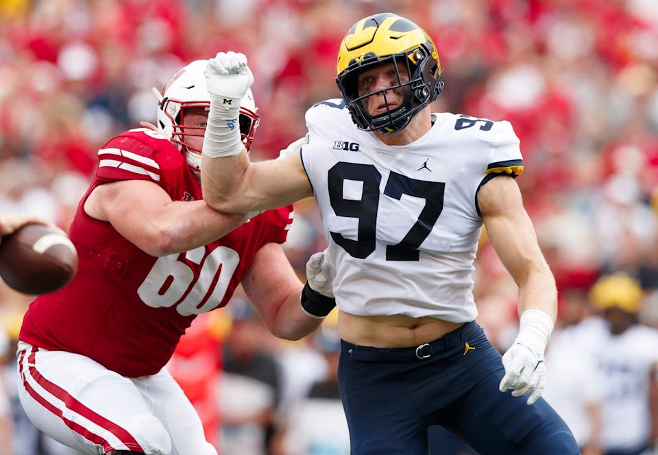 Michigan Wolverines defensive end Aidan Hutchinson (97) rushes the quarterback as Wisconsin Badgers offensive lineman Logan Bruss (60) blocks during the third quarter Oct. 2, 2021 at Camp Randall Stadium in Madison, Wisconsin.
