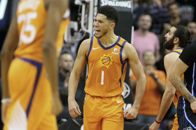 Phoenix Suns' Devin Booker (1) celebrate after back-to-back three-point baskets and a turnover against the Orlando Magic during the second half of an NBA basketball game Friday, Jan. 10, 2020, in Phoenix. (AP Photo/Darryl Webb)