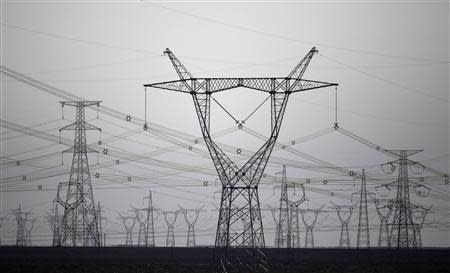 High voltage power lines are seen near a wind farm in Guazhou, 950km (590 miles) northwest of Lanzhou, Gansu Province September 15, 2013. REUTERS/Carlos Barria