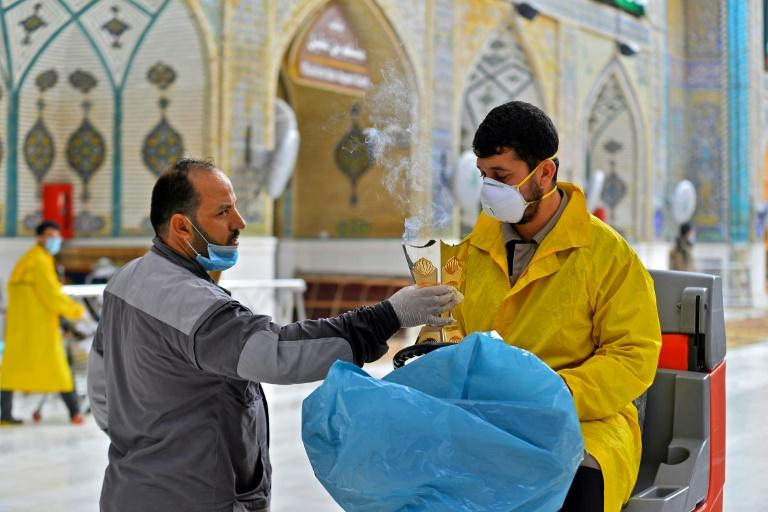 A sanitary worker, wearing a mask, in the courtyard of the shrine of Imam Ali in the holy Iraqi city of Najaf