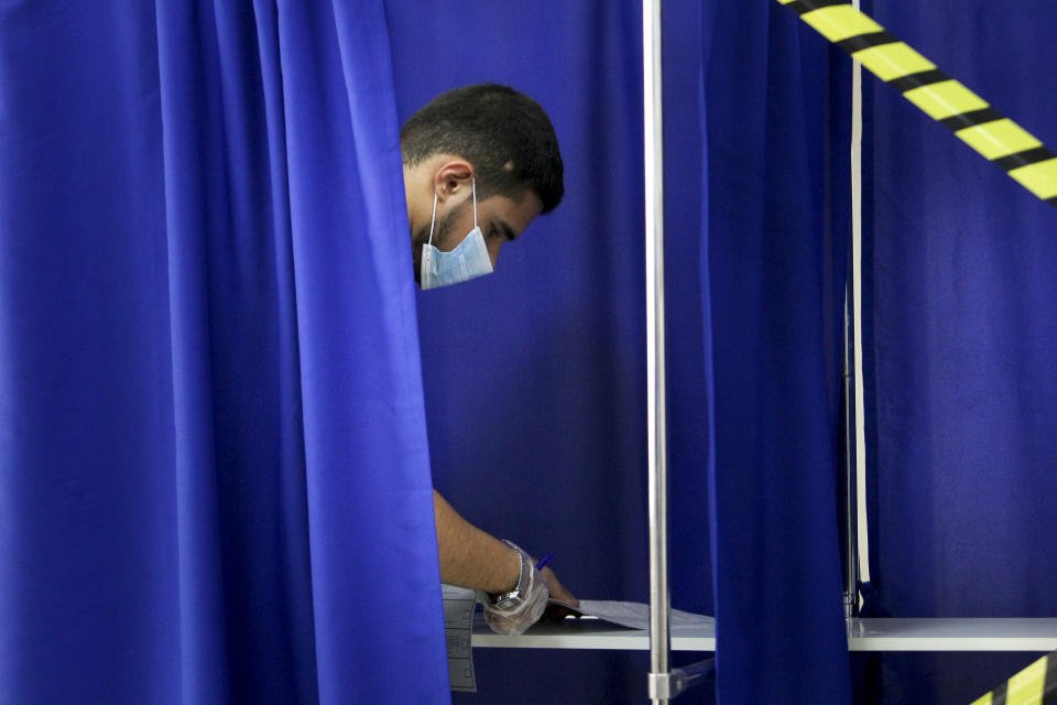 A Chechen man reads his ballots in a voting booth at a polling station during the Parliamentary elections in Grozny, Russia, Saturday, Sept. 18, 2021. Sunday will be the last of three days voting for a new parliament, but there seems to be no expectation that United Russia, the party devoted to President Vladimir Putin, will lose its dominance in the State Duma. (AP Photo/Musa Sadulayev)