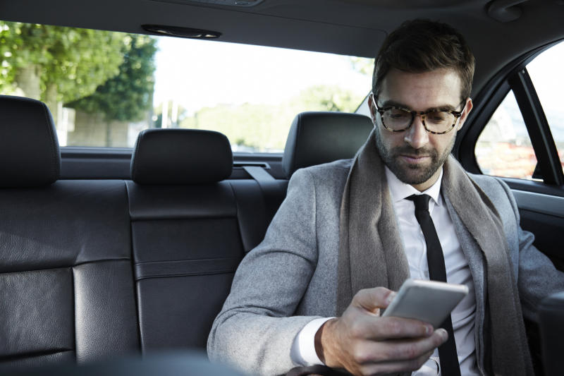 A man in a suit in the back of a car looking at his smartphone.