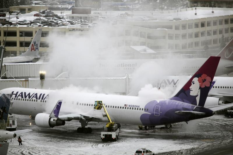 A Hawaiian Airlines plane, delayed for approximately 4 hours, undergoes de-icing before takeoff at Seattle-Tacoma International Airport