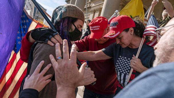 PHOTO: Trump supporters demonstrating during the election results, at right, pray with a counter protester after the presidential election was called for Joe Biden outside the State Capitol in Lansing, Mich., Nov. 7, 2020. (David Goldman/AP)