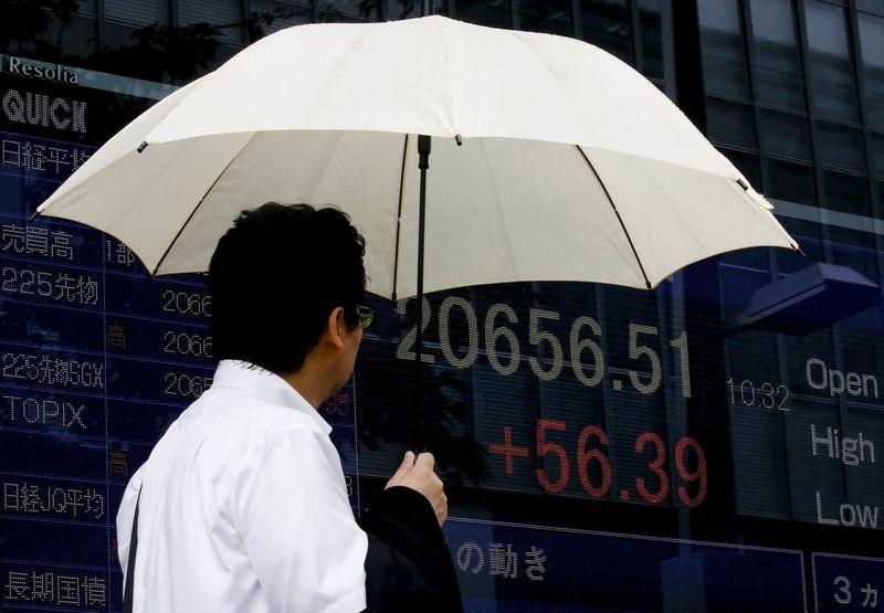 A man looks at a board displaying the Nikkei average in Tokyo July 17, 2015. REUTERS/Thomas Peter
