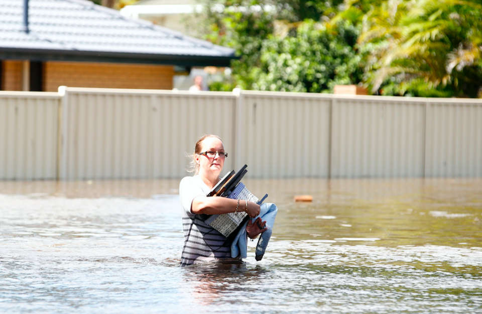 A south east Queensland woman carries belongings to safety during floods earlier this week. Photo: AAP