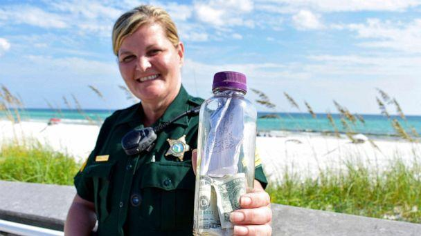 PHOTO: In this undated photo provided by the Walton County Sheriff's Office Sgt. Paula Pendleton poses with a bottle that washed ashore near Miramar Beach, Fla. (Corey Dobridnia/Walton County Sheriff's Office via AP)