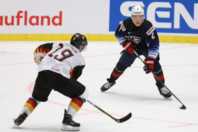 Germany's Dennis Lobach defends as United States' Jordan Harris carries the puck during the 2020 IIHF World Junior Ice Hockey Championships Group B match between Germany and USA in Ostrava, Czech Republic, Friday, Dec. 27, 2019. (Petr Sznapka/CTK via AP)