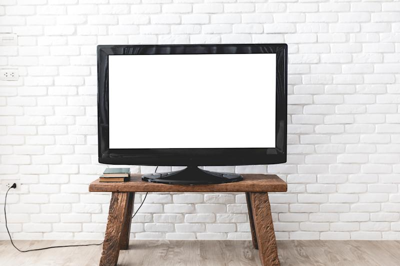 A flat screen television sitting on a wooden table against a white brick wall.